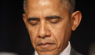 President Barack Obama closes his eyes as a prayer is offered at the National Prayer Breakfast in Washington, Thursday, Feb. 6, 2014. (AP Photo/Charles Dharapak)