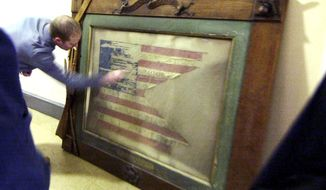 FOR USE IN WEEKEND EDITIONS FEB. 8-9 - In this Jan. 22, 2014 photo, Steve Purtell points to a portion of a Civil War Flag found in the basement of the Lowell Memorial Auditorium in Lowell, Mass. The tattered, faded and worn flag accompanied Union troops on a Louisiana battlefield in 1863,  (AP Photo/Lowell Sun, Bob Whitaker)
