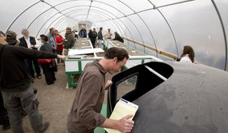 ADVANCE FOR MONDAY FEB. 10 - In this Feb. 1, 2014 photo, John Sammons checks out the fish tank at a Project Growth Open House in Fort Worth, Texas.  Known as Project Growth, the urban farm just minutes from downtown Fort Worth is flourishing. The farm is an initiative of Feed by Grace, a nonprofit organization that ministers to the homeless. Not quite 2 years old, Project Growth trains and employs homeless people to grow organic vegetables, make compost and install gardens around the community. (AP Photo/The Fort Worth Star-Telegram, Joyce Marshall)  MAGS OUT; (FORT WORTH WEEKLY, 360 WEST); INTERNET OUT