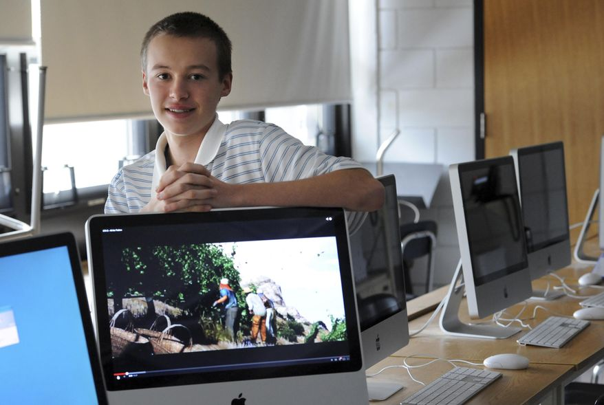 FOR USE IN WEEKEND EDITIONS FEB. 8-9 -  In this Jan. 27, 2014 photo, Matt West poses among computers at Nauset Regional High School in North Eastham, Mass. In an effort to keep children younger than himself away from violent video games, West has started a club to design and market nonviolent games. (AP Photo/Cape Cod Times, Merrily Cassidy) MANDATORY CREDIT. INTERNET OUT. MAGS OUT. TV OUT. NO ARCHIVING WITHOUT PERMISSION.