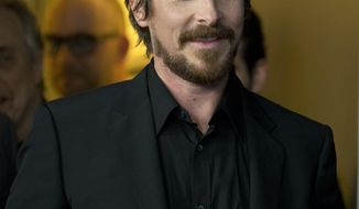 Actor Christian Bale jokingly arrives at the photo call for the film American Hustle during the International Film Festival Berlinale, in Berlin, Friday, Feb. 7, 2014. (AP Photo/Axel Schmidt)