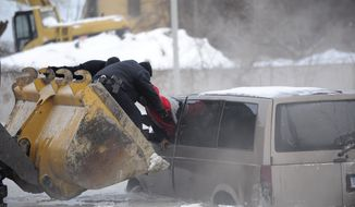 Detroit police use the scoop of a front-end loader to carry two people stranded in a minivan to safety after street flooding caused by a water main break on Friday, Feb. 7, 2014 on Detroit's east side. Several vehicles were stuck in water and ice, prompting a rescue by police officers on construction equipment. The break was reported about 5 a.m. Friday in the area of Gratiot Avenue at Conner Street. The scoop of a front-end loader was used to carry two people stranded in a minivan. Crews also worked to clear ice and water from the area, which is closed to traffic. No injuries were reported. (AP Photo/The Detroit New, David Coates) DETROIT FREE PRESS OUT; HUFFINGTON POST OUT, NO SALES, NO MAGS, MANDATORY CREDIT