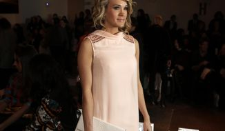 Singer Carrie Underwood poses for photos before the Peter Som Fall 2014 collection is modeled during Fashion Week in New York,  Friday, Feb. 7, 2014. (AP Photo/Richard Drew)