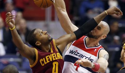 Washington Wizards center Marcin Gortat (4), from Poland, dunks the ball and takes it on the nose from Cleveland Cavaliers guard C.J. Miles (0) in the first half of an NBA basketball game on Friday, Feb. 7, 2014, in Washington. (AP Photo/Alex Brandon)