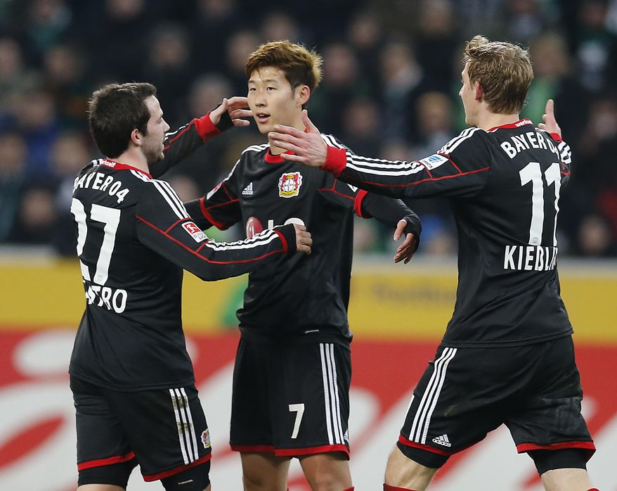 Leverkusen's Son Heung-min Son of South Korea , center, celebrates with Leverkusen's Gonzalo Castro, left, and Leverkusen's Stefan Kiessling after scoring  during the German first division Bundesliga soccer match between Borussia Moenchengladbach and Bayer 04 Leverkusen in Moenchengladbach, Germany, Friday, Feb. 7, 2014. (AP Photo/Frank Augstein)