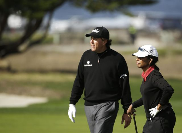 Phil Mickelson, left, talks with former United States Secretary of State Condoleezza Rice while walking up the 12th fairway of the Monterey Peninsula Country Club Shore Course during the first round of the AT&T Pebble Beach Pro-Am golf tournament Thursday, Feb. 6, 2014, in Pebble Beach, Calif. (AP Photo/Eric Risberg)