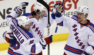 New York Rangers' Benoit Pouliot, center, celebrates his goal with Mats Zuccarello (36) and Anton Stralman (6) during the first period of an NHL hockey game against the Pittsburgh Penguins in Pittsburgh, Friday, Feb. 7, 2014. (AP Photo/Gene J. Puskar)