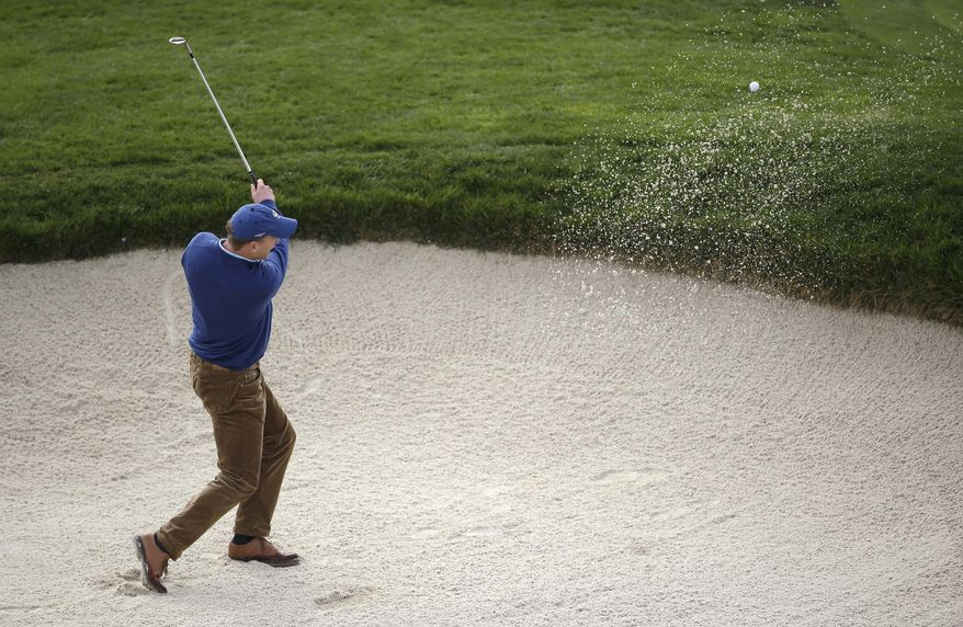Denver Broncos quarterback Peyton Manning hits the ball out of a bunker up to the seventh green of Pebble Beach Golf Links during the second round of the AT&T Pebble Beach Pro-Am golf tournament, Friday, Feb. 7, 2014, in Pebble Beach, Calif. (AP Photo/Eric Risberg)