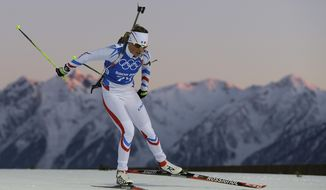 Marie Dorin-Habert of France skis past mountain tops during a Biathlon training session at the 2014 Winter Olympics, Thursday, Feb. 6, 2014, in Krasnaya Polyana, Russia. (AP Photo/Kirsty Wigglesworth)