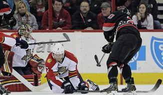 Carolina Hurricanes' Riley Nash (20) shoots against  Florida Panthers' Dmitry Kulikov (7), of Russia, and goalie Tim Thomas during the first period of an NHL hockey game in Raleigh, N.C., Friday, Feb. 7, 2014. Nash scored on the shot. (AP Photo/Gerry Broome)