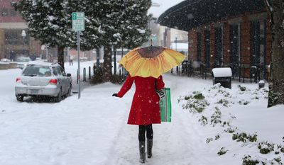 A brightly-dressed Stephanie Gibbs breaks up the monochrome of a snowy afternoon as she makes her way down 10th Ave. in downtown Eugene, Ore. on Friday, Feb. 7, 2014, on her way to the Eugene Public Library.  Snowfall starting late in the morning Friday will be widespread, dropping a foot or more in mountainous parts of Southern Oregon and 2 to 8 inches in Western Oregon valleys that got slammed Thursday, the National Weather Service said. (AP Photo/The Register-Guard, Brian Davies)