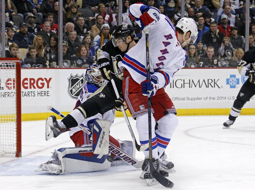 Pittsburgh Penguins' Chris Kunitz (14) leaps out of the way of a shot between New York Rangers goalie Henrik Lundqvist (30) and New York Rangers' Ryan McDonagh (27) during the second period of an NHL hockey game in Pittsburgh, Friday, Feb. 7, 2014. (AP Photo/Gene J. Puskar)