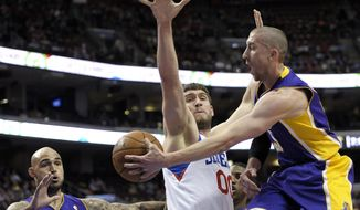 Los Angeles Lakers' Steve Blake, right, passes the ball to Robert Sacre, left, as Philadelphia 76ers' Spencer Hawes, center, defends during the first half of an NBA basketball game on Friday, Feb. 7, 2014, in Philadelphia. (AP Photo/Michael Perez)