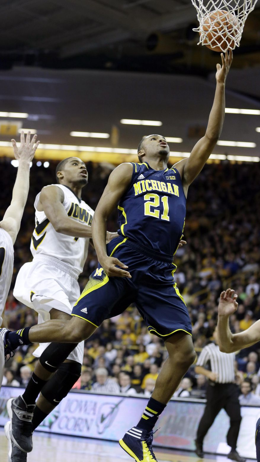 Michigan guard Zak Irvin drives to the basket past Iowa forward Melsahn Basabe, left, during the first half of an NCAA college basketball game, Saturday, Feb. 8, 2014, in Iowa City, Iowa. (AP Photo/Charlie Neibergall)