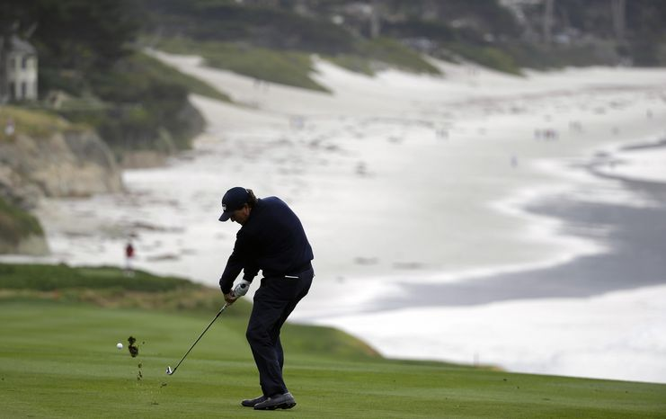 Phil Mickelson hits from the fairway down to the ninth green of the Pebble Beach Golf Links during the second round of the AT&T Pebble Beach Pro-Am golf tournament on Friday, Feb. 7, 2014, in Pebble Beach, Calif. (AP Photo/Eric Risberg)