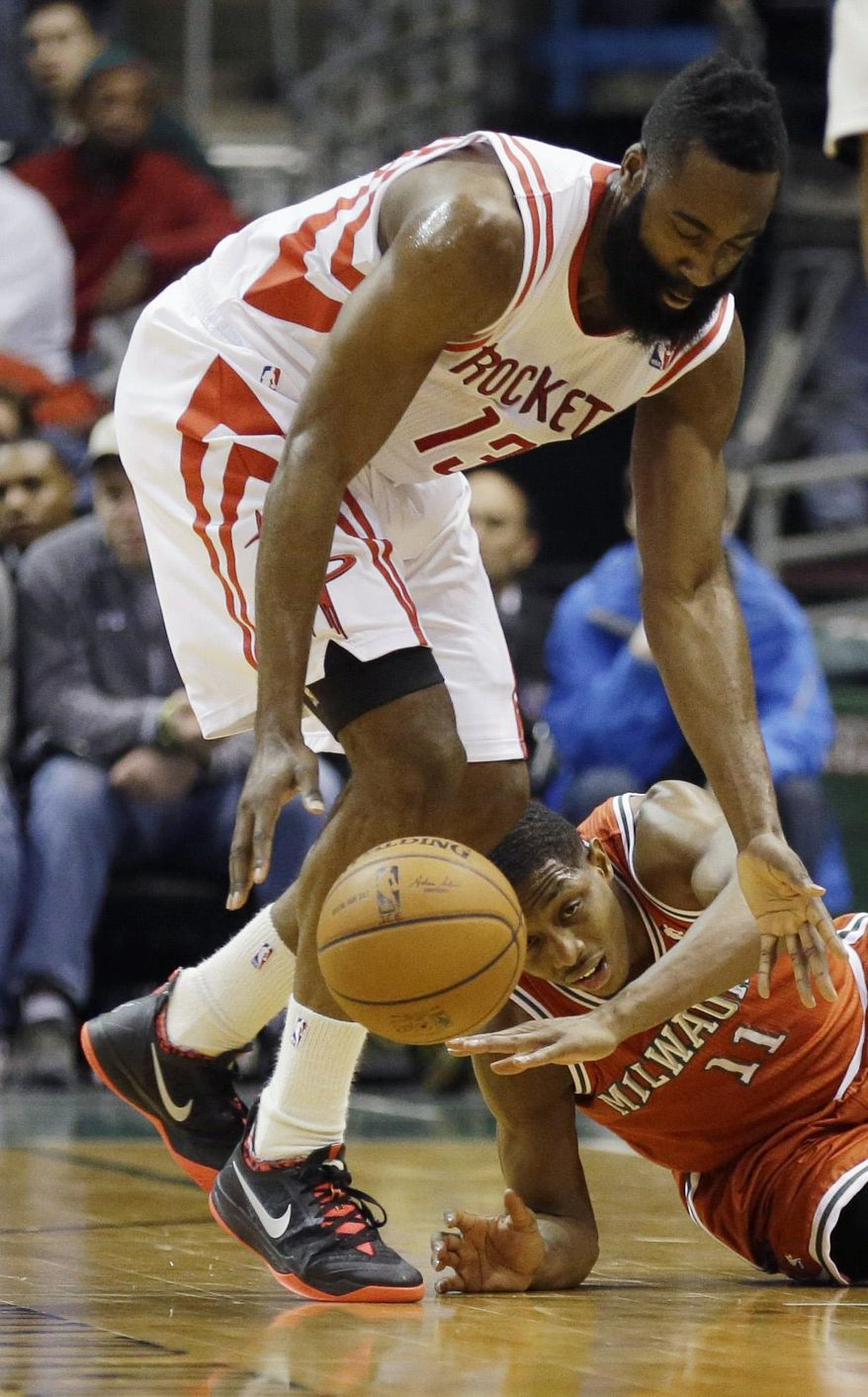 Houston Rockets' James Harden (13) steals the ball from Milwaukee Bucks' Brandon Knight (11) during the first half of an NBA basketball game, Saturday, Feb. 8, 2014, in Milwaukee. (AP Photo/Jeffrey Phelps)