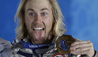 Gold medal winner Sage Kotsenburg, of the United States, holds up his medal during the medal ceremony for the Snowboard Men's Slopestyle competition at the 2014 Winter Olympics, Saturday, Feb. 8, 2014, in Sochi, Russia. (AP Photo/David J. Phillip )