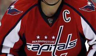 Washington Capitals right wing Alex Ovechkin reacts as he comes to the bench after a collision with Winnipeg Jets left wing Andrew Ladd during the third period of an NHL hockey game, Thursday, Feb. 6, 2014, in Washington. Ovechkin returned to the game, which the Capitals won 4-2. (AP Photo/Alex Brandon)