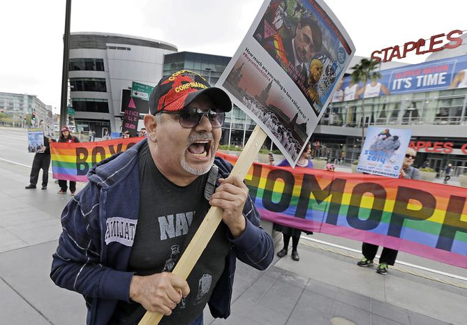 """Dave Lara, of Los Angeles, joins demonstrators from a coalition of gay rights organizations, religious and political groups protest the treatment of gays in Russia, whose coastal city of Sochi hosts the 22nd Olympic Winter Games, outside the final stop of the """"Road to Sochi,"""" a traveling exhibit hosted by the U.S. Olympic Committee, at LALive in downtown Los Angeles Friday, Feb. 7, 2014.  (AP Photo/Reed Saxon)"""
