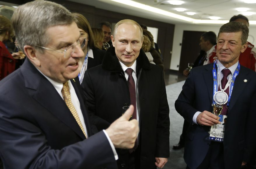 Russian President Vladimir Putin, center, talks with International Olympic Committee President Thomas Bach, left, and Deputy Prime Minister Dmitry Kozak, right, in the presidential lounge following the opening ceremony of the 2014 Winter Olympics, Friday, Feb. 7, 2014, in Sochi, Russia. (AP Photo/David Goldman, Pool)