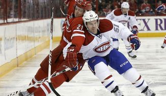 Carolina Hurricanes' Drayson Bowman (21) and Montreal Canadiens' David Desharnais (51) chase the puck during the second period of an NHL hockey game in Raleigh, N.C., Saturday, Feb. 8, 2014. (AP Photo/Gerry Broome)