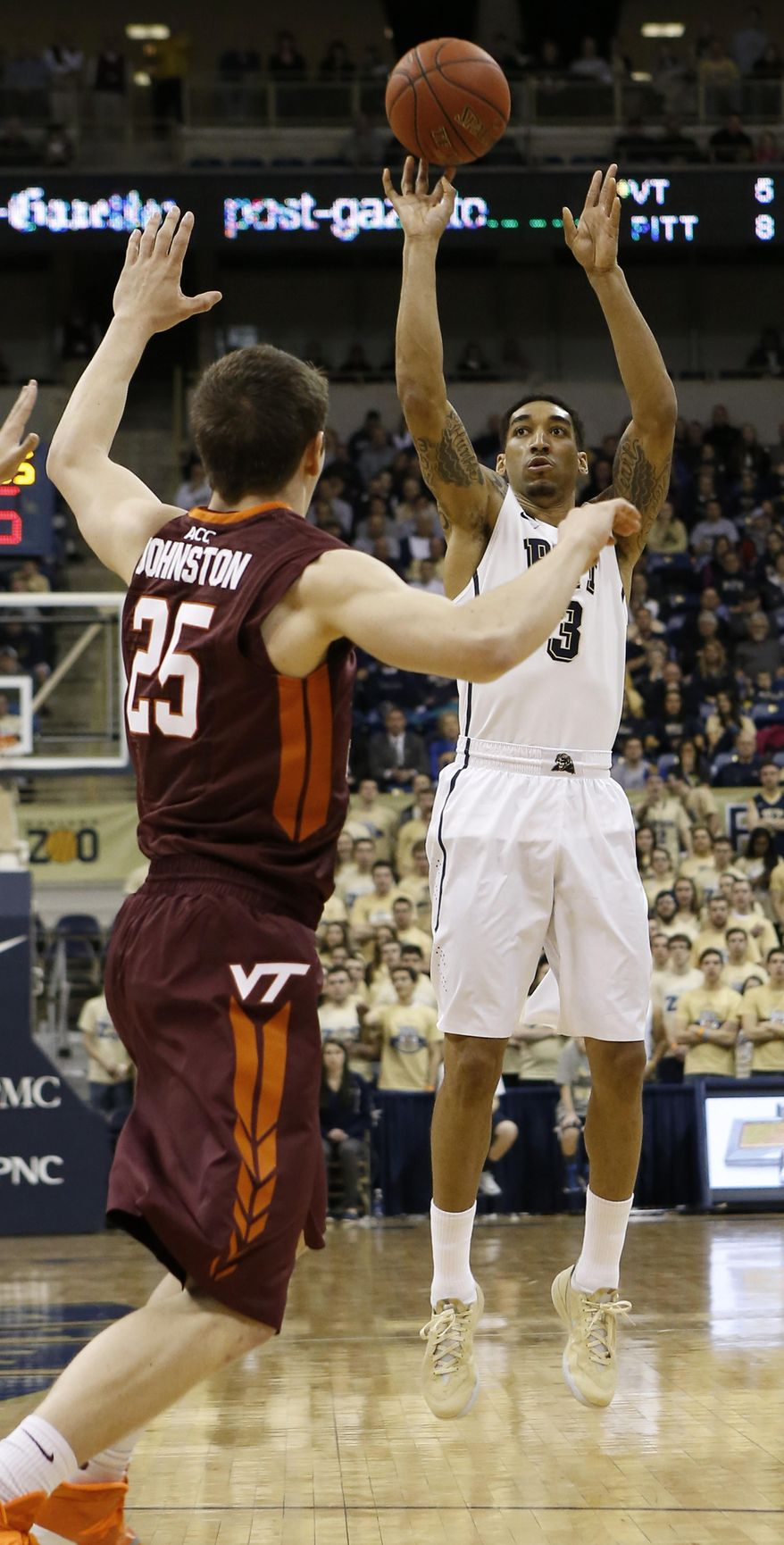 Pittsburgh's Cameron Wright (3) hits a 3-point shot over Virginia Tech's Will Johnston (25) during the first half of the NCAA college basketball game on Saturday, Feb. 8, 2014, in Pittsburgh. (AP Photo/Keith Srakocic)