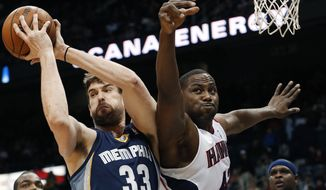 Memphis Grizzlies center Marc Gasol (33) pulls down a rebound against Atlanta Hawks power forward Elton Brand (42) in the first half of an NBA basketball game Saturday, Feb. 8, 2014, in Atlanta.  (AP Photo/John Bazemore)