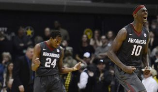 Arkansas guard Michael Qualls (24) and forward Bobby Portis (10) celebrate after Arkansas defeated Vanderbilt 77-75 in an NCAA college basketball game on Saturday, Feb. 8, 2014, in Nashville, Tenn.  (AP Photo/Mark Zaleski)