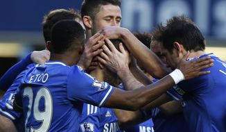 Chelsea's Eden Hazard, center, is mobbed by teammates as he celebrates his penalty goal and his third goal against Newcastle United during their English Premier League soccer match at Stamford Bridge, London, Saturday, Feb. 8, 2014. (AP Photo/Sang Tan)