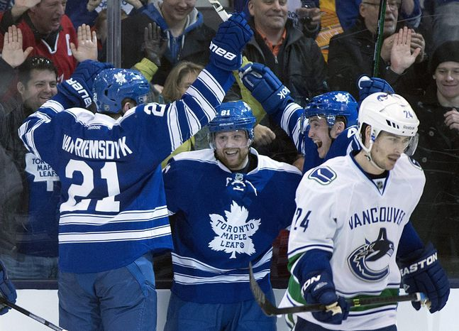 Toronto Maple Leafs' James van Riemsdyk, left, celebrates his goal with teammates Tyler Bozak and Phil Kessel, center, as Vancouver Canucks defenseman Raphael Diaz (24) skates away during the third period of an NHL hockey game, Saturday, Feb. 8, 2014 in Toronto. (AP Photo/The Canadian Press, Frank Gunn)
