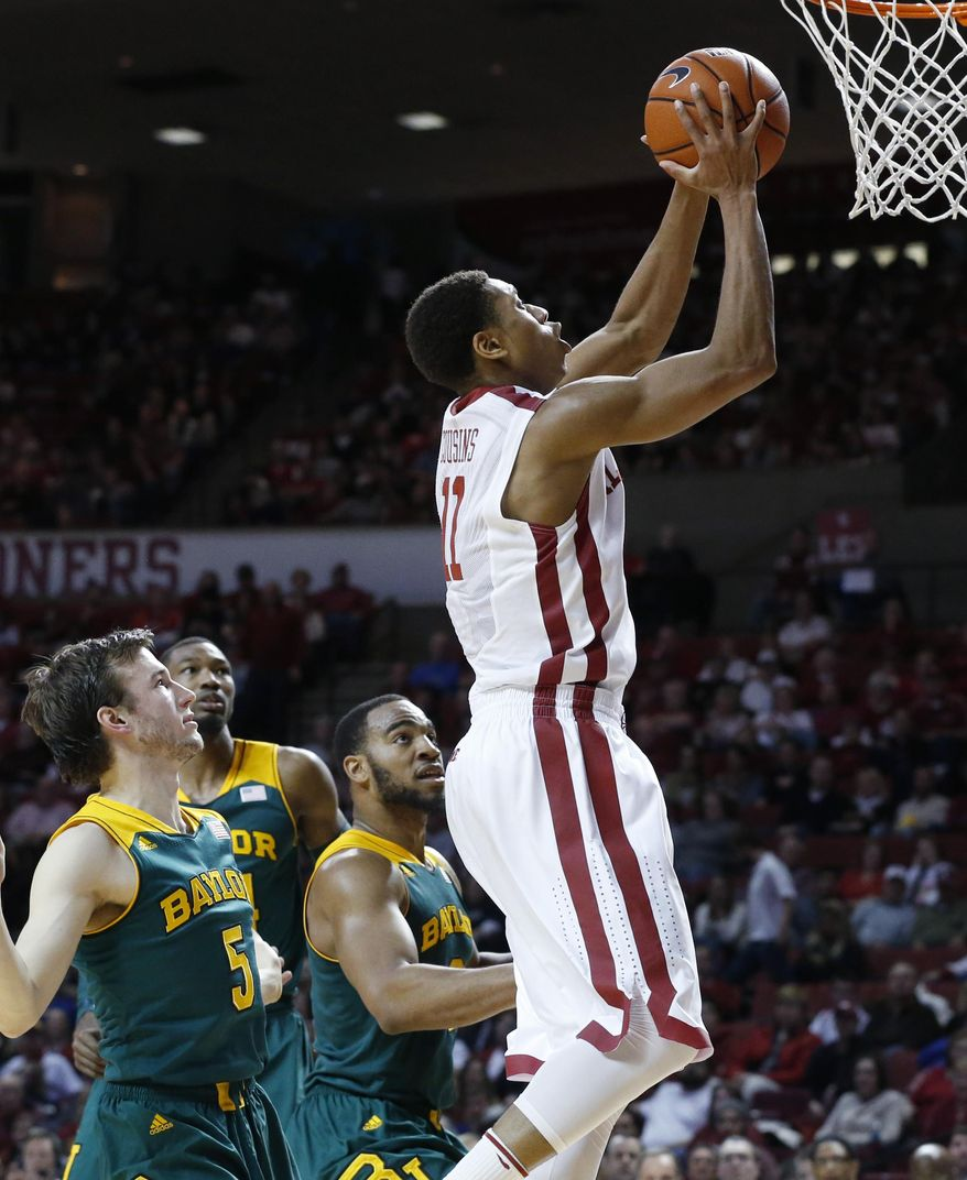 Oklahoma guard Isaiah Cousins (11) shoots in front of Baylor guard Brady Heslip (5), forward Cory Jefferson, back left, and forward Rico Gathers (2) in the second half of an NCAA college basketball game in Norman, Okla., Saturday, Feb. 8, 2014. Oklahoma won 88-72. (AP Photo/Sue Ogrocki)