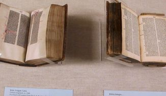 A hand-lettered manuscript Bible dating to around 1240 (left) is seen next to a printed Bible of the same size from 1495 at the University of South Carolina in Columbia, S.C., on Thursday, Feb. 6, 2014. The university is, for the first time in one exhibit, displaying its collection of early printed books that provide a glimpse of the era when printed books were replacing hand-copied manuscripts. (AP Photo/Bruce Smith)