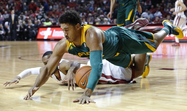 Baylor guard Ish Wainright, top, dives over Oklahoma guard Jordan Woodard for a loose ball in the first half of an NCAA college basketball game in Norman, Okla., Saturday, Feb. 8, 2014. (AP Photo/Sue Ogrocki)