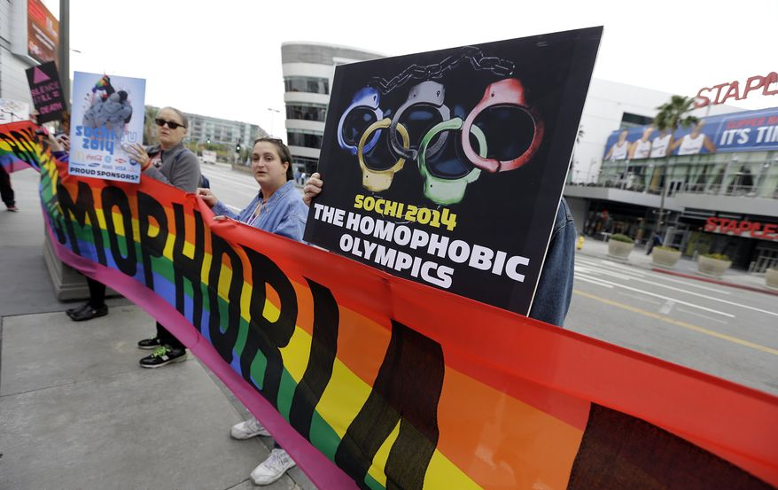 """Demonstrators from a coalition of gay rights organizations, religious and political groups protest the treatment of gays in Russia, whose coastal city of Sochi hosts the 22nd Olympic Winter Games, outside the final stop of the """"Road to Sochi,"""" a traveling exhibit hosted by the U.S. Olympic Committee, at LALive in downtown Los Angeles Friday, Feb. 7, 2014.  (AP Photo/Reed Saxon)"""