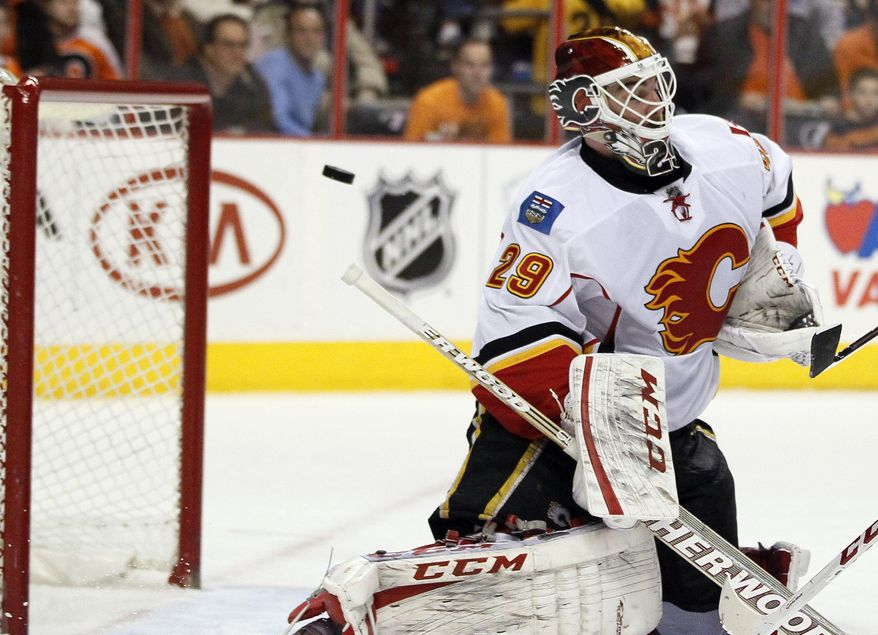 Calgary Flames goalie Reto Barra is unable to stop a shot for a goal by Philadelphia Flyers' Brayden Schenn during the second period of an NHL hockey game, Saturday, Feb. 8, 2014, in Philadelphia. (AP Photo/Tom Mihalek)