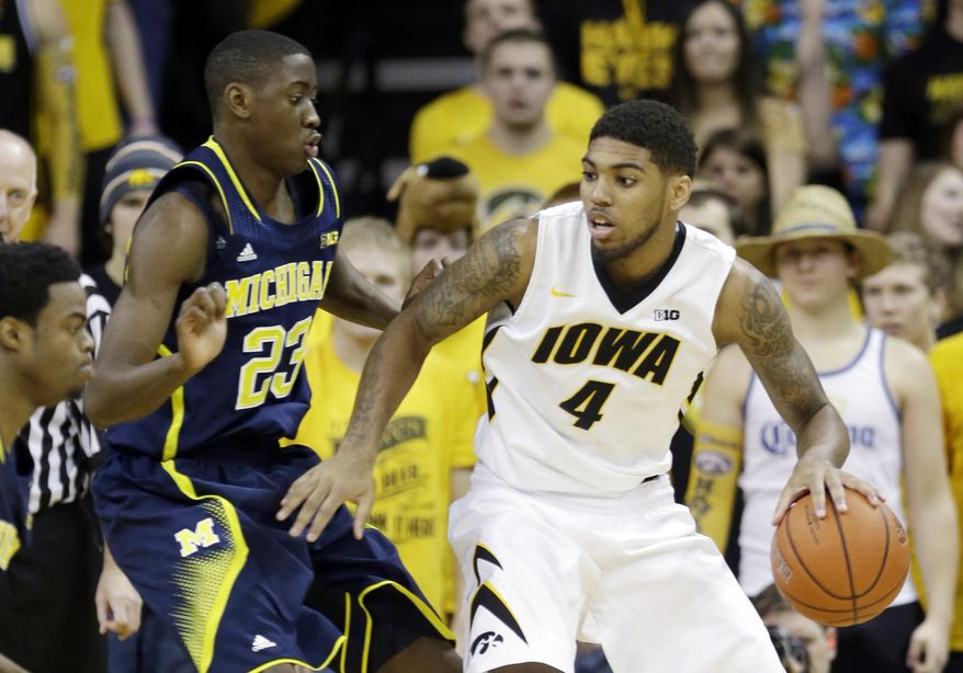 Iowa guard Devyn Marble, right, looks to drive past Michigan guard Caris LeVert (23) during the first half of an NCAA college basketball game, Saturday, Feb. 8, 2014, in Iowa City, Iowa. (AP Photo/Charlie Neibergall)