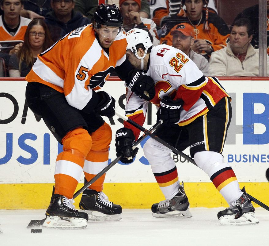 Philadelphia Flyers' Braydon Coburn, left, and Calgary Flames' Lee Stempniak, right, dig for the loose puck along the boards during the first period of an NHL hockey game, Saturday, Feb. 8, 2014, in Philadelphia. (AP Photo/Tom Mihalek)