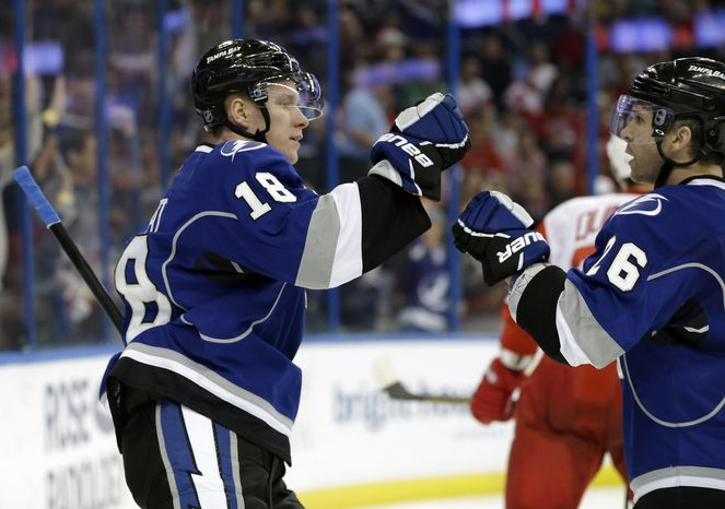 Tampa Bay Lightning left wing Ondrej Palat (18) celebrates his goal against the Detroit Red Wings with teammate Martin St. Louis (26) during the second period of an NHL hockey game, Saturday, Feb. 8, 2014, in Tampa, Fla. (AP Photo/Chris O'Meara)