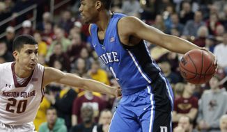 Duke forward Jabari Parker (1) holds the ball away from Boston College guard Lonnie Jackson (20) after Parker pulled in a defensive rebound during the first half of their NCAA college basketball game on the Boston College campus in Boston, Saturday, Feb. 8, 2014. (AP Photo/Stephan Savoia)