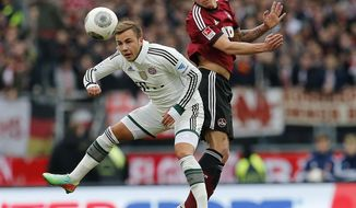 Nuremberg's Mike Frantz, right, and Bayern's Mario Goetze challenge for the ball during a   German first   division Bundesliga soccer match  between 1.FC Nuremberg and Bayern Munich in Nuremberg, Germany, Saturday, Feb. 8, 2014.  (AP Photo/Michael Probst)
