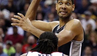 San Antonio Spurs forward Tim Duncan, top, looks to pass over Washington Wizards forward Nene (42), from Brazil, in the second half of an NBA basketball game on Wednesday, Feb. 5, 2014, in Washington. Duncan had 31 points and the Spurs won 125-118 in double overtime. (AP Photo/Alex Brandon)