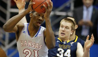 Kansas center Joel Embiid (21) rebounds against West Virginia forward Kevin Noreen (34) during the first half of an NCAA college basketball game in Lawrence, Kan., Saturday, Feb. 8, 2014. (AP Photo/Orlin Wagner)