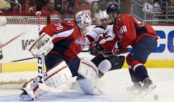 Washington Capitals goalie Braden Holtby, left, and defenseman Connor Carrick, right, battle New Jersey Devils right wing Stephen Gionta during the first period of an NHL hockey game on Saturday, Feb. 8, 2014, in Washington. (AP Photo/ Evan Vucci)