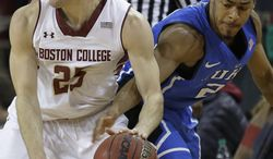 Duke guard Quinn Cook (2) reaches in to steal the ball away from Boston College guard Joe Rahon (25) during the second half of their NCAA  college basketball game on the Boston College campus in Boston, Saturday, Feb. 8, 2014. Duke defeated Boston College 89-68. (AP Photo/Stephan Savoia)