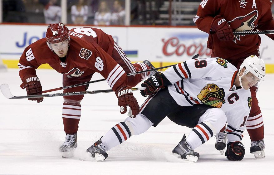Chicago Blackhawks' Jonathan Toews, right, gets tangled up with Phoenix Coyotes' Mikkel Boedker (89), of Denmark, during the first period in an NHL hockey game Friday Feb. 7, 2014, in Glendale, Ariz.  The Coyotes defeated the Blackhawks 2-0. (AP Photo/Ross D. Franklin)