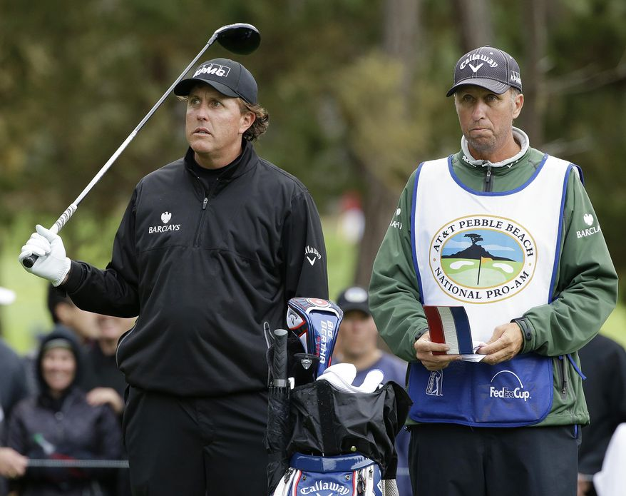 "Phil Mickelson, left, prepares to hit on the seventh tee Saturday, Feb. 8, 2014, during the third round of the AT&T Pebble Beach Pro-Am golf tournament on the Spyglass Hill Golf Course in Pebble Beach, Calif. At right is his caddie Jim ""Bones"" Mackay. (AP Photo/Ben Margot)"