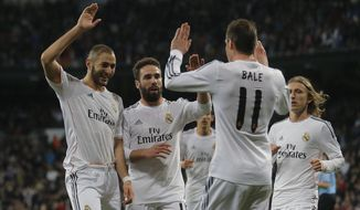 Real Madrid's Karim Benzema from France, left, celebrates his goal with Real Madrid's Gareth Bale from Great Britain, second right, and teammates during a Spanish La Liga soccer match between Real Madrid and Villarreal at the Bernabeu stadium stadium in Madrid, Spain, Saturday, Feb. 8, 2014. (AP Photo/Andres Kudacki)