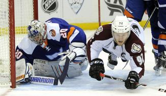 Colorado Avalanche's Gabriel Landeskog (92) crashes into New York Islanders goalie Evgeni Nabokov (20) leaving the puck behind for Avalanche' Nathan MacKinnon to score in the first period of an NHL hockey game on Saturday, Feb. 8, 2014, in Uniondale, N.Y. (AP Photo/Kathy Kmonicek)