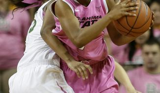Oklahoma State's Brittany Atkins, right, prepares to pass the ball as Baylor's Nina Davis (13) defends in the second half of an NCAA college basketball game on Sunday, Feb. 9, 2014, in Waco, Texas.  Both teams wore uniforms accented with pink for breast cancer awareness. Baylor won 81-64. (AP Photo/Tony Gutierrez)