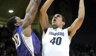 Josh Scott of Colorado shoots over Shawn Kemp of Washington during the first half of an NCAA college basketball game in Boulder, Colo., Sunday, Feb. 9, 2014. (AP Photo/Daily Camera, Cliff Grassmick)
